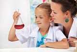 Young student girl in chemistry class with her teacher