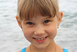 portrait of smiling little funny blonde girl
