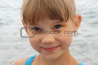 smiling blue-eyed baby girl on sea background