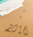 2016 new year digits written on beach sand