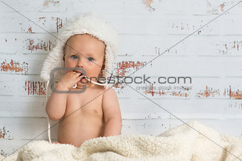 Baby girl in a cap enjoying warmth of the room