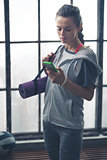 Woman in workout gear in loft gym checking mobile phone