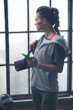 Woman in workout gear holding phone and yoga mat in loft gym