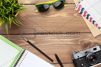 Camera, sunglasses and supplies on office desk