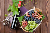 Red wine bottle and colorful grapes