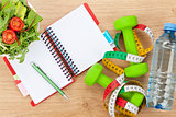 Healthy food, dumbells, tape measure and notepad for copy space