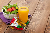 Healthy food and tape measure over wooden table