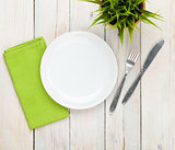 Empty plate and silverware over white wooden table background