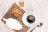 Coffee cup, heart shaped gingerbread cookies and milk pitcher