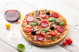 Italian pizza with pepperoni, tomatoes, olives, basil and red wi