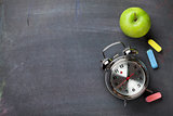 Colorful chalk, alarm clock and apple on blackboard background