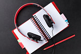 Headphones over notepad on desk