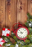 Christmas wooden background with clock, fir tree and gift boxes