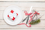 Gift box on plate, silverware and christmas decor