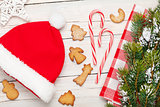 Christmas santa hat, gingerbread cookies and snow fir tree