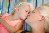 Little Girl Laying on Blanket Kisses Her Mommy