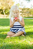 Little Girl Sitting and Eating Apple Outside