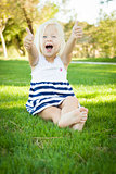 Cute Little Girl with Thumbs Up in the Grass