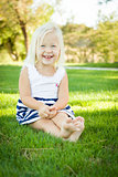Cute Little Girl Sitting and Laughing in the Grass