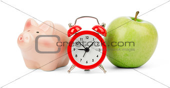 Fresh apple with alarm clock and piggy bank