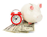 Piggy bank with cash and alarm clock