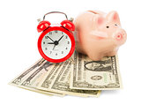 Piggy bank with money and alarm clock