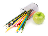 Fallen pencil cup with crayons and green  apple