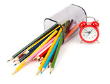 Fallen pencil cup with crayons and red alarm clock