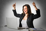Happy woman in office with thumbs up