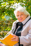 portrait of a happy grandmother on a park bench