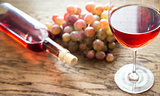 Glass of rose wine with bunch of grape