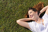 Relaxed happy woman resting on the grass looking at side