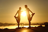 Silhouette of a fitness couple stretching at sunset