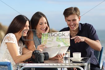 Group of young tourist friends consulting a paper map