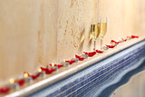 Candles and rose petals wit a champagne cups in a spa celebration concept