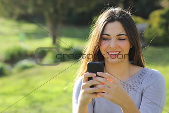 Casual woman happy using a smart phone in a park