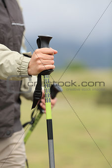 Close up of a hiker hands holding a hiking pole while walking