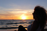 Woman silhouette watching a sunset in Ibiza