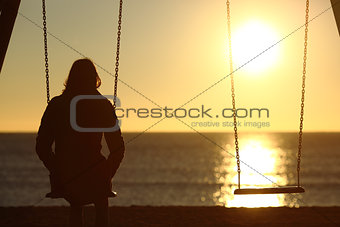 Lonely woman watching sunset alone in winter
