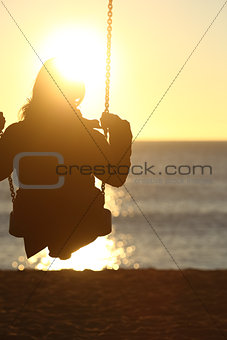 Woman silhouette swinging at sunset on the beach
