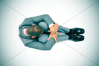 businessman curled up in the floor with his head between his kne