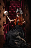 Horror photo: beautiful goth girl in black dress holds the skull