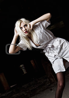 A beautiful scared young girl in the image of nurse among the dark