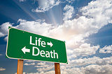 Life and Death Green Road Sign Over Clouds