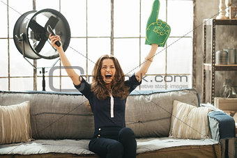 Football fan woman watching tv in loft apartment and rejoicing