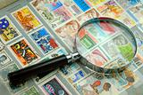 Collection of stamps and magnifier