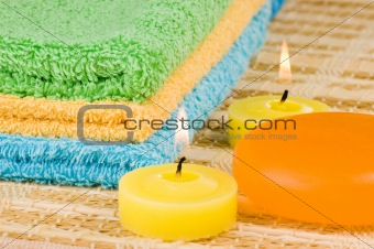 Towels of different colours soap and candles