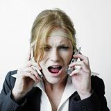 Stressed woman on two phones