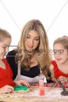 beautiful mother and twin daughters decorating cookies isolated on white