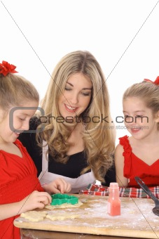 beautiful mother and twin daughters decorating cookies together isolated on white